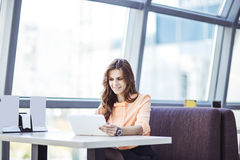 Successful business woman with digital tablet sitting at Desk in the spacious office Royalty Free Stock Image