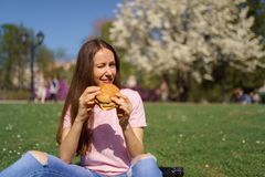 Successful business woman eating fast food burger cheesburger enjoys her leisure free time in a park with blossoming royalty free stock images