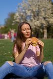 Successful business woman eating fast food burger cheesburger enjoys her leisure free time in a park with blossoming royalty free stock photo