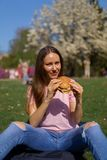 Successful business woman eating fast food burger cheesburger enjoys her leisure free time in a park with blossoming stock image