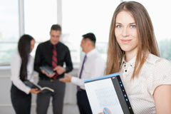 Successful business woman at foreground and business team at background Stock Photos