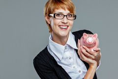 Successful business woman holding a little piggy bank Stock Images
