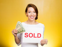 Successful business woman holding sold sign and cash dollar bills. Financial reward. Closeup portrait happy excited successful young business woman holding red Royalty Free Stock Photo