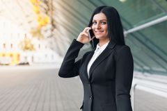 Successful business woman with mobile phone in an urban setting. Young successful business woman with mobile phone in an urban setting Stock Images