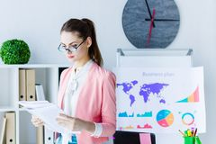 Successful business woman at modern office. Beautiful professional business woman wear glasses and colorful strict cloth in modern office viewing browse stock photo