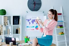Successful business woman at modern office. Young lazy business woman in pink blazer is idling at workplace. Beautiful girl employee is smiling and doing makeup royalty free stock photo