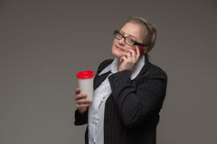 Successful business woman is not young in a suit with coffee tal. Successful business woman is not young in a suit talking on the phone Royalty Free Stock Image