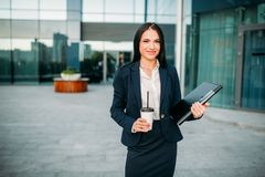Successful business woman with notebook and coffee. In hands. Modern building, financial center, cityscape. Female businessperson in suit outdoor Royalty Free Stock Photos
