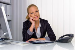 Successful business woman at the office. A young, successful business woman sitting at her desk in the office Stock Photos