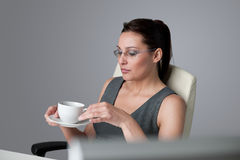Successful business woman at office having coffee. Successful business woman at office having cup of coffee sitting at computer desk Royalty Free Stock Photos