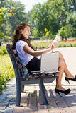 Successful business woman in park outdoor. Successful business woman sitting on a park bench and reading newspaper Stock Photography