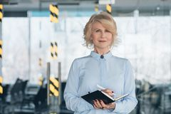 Successful business woman professional career. Successful professional career. Mature successful business woman standing with pen and notebook at conference hall royalty free stock photos