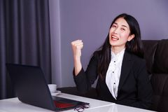 Successful business woman raising arm in happiness with laptop c Royalty Free Stock Images