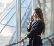 Successful business woman with a smartphone, standing in front of a window in a modern office. Confident successful business woman with a smartphone, standing Stock Photography