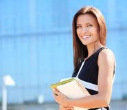 Successful business woman smiling. Portrait of a successful business woman smiling. Beautiful young female executive in an urban setting Royalty Free Stock Images