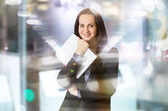Successful business woman smiling portrait with note pad. Portrait in office against glass reflection Royalty Free Stock Photography