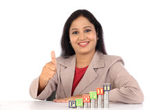 Successful business woman with stack of coins and making thumb up Royalty Free Stock Images