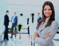 Successful business woman standing with her staff in background at office. Stock Photos