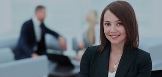 Successful business woman standing with her staff in background Stock Photography