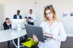 Successful business woman standing with laptop with her staff in background at modern bright office royalty free stock image