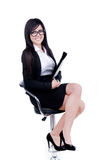 Successful Business woman. Studio shot of a successful business woman wearing nerd glasses sitting down holding a file Stock Photography