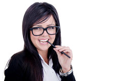 Successful Business woman. Studio shot of a successful business woman wearing nerd glasses smiling and biting a pencil Royalty Free Stock Photos