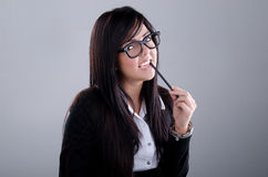 Successful Business woman. Studio shot of a successful business woman wearing nerd glasses smiling and biting a pencil Stock Photo