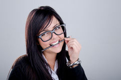 Successful Business woman. Studio shot of a successful business woman wearing nerd glasses smiling and biting a pencil Stock Photos
