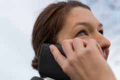 Successful business woman talking on cellphone while walking out Stock Image