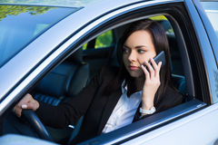 Successful business woman talking on smartphone in her car Royalty Free Stock Photos