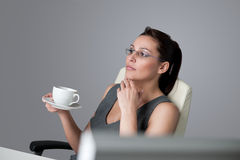Successful business woman think at office. Successful business woman at office having cup of coffee sitting at computer desk Royalty Free Stock Photography
