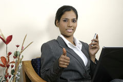 Successful business woman thumbs up with laptop. Young Indian business woman thumbs up and working on laptop Royalty Free Stock Photos