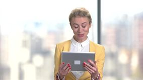Successful business woman using digital tablet. Young cheerful female speaking via internet using pc tablet, front view stock video