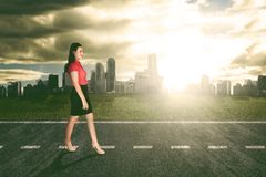 Confident business woman walking on the road. Successful business woman walking with bright sunlight and office buildings background Royalty Free Stock Image