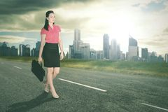 Successful business woman walking with bright sunlight and office buildings background.  Royalty Free Stock Photos
