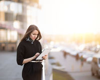 Successful business woman working on a digital tablet near an office building Royalty Free Stock Photo