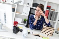 A young girl sits in the office at a computer desk, leans on a pile of books, straightens glasses and looks at the royalty free stock image