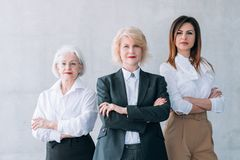 Successful business women ambitious female team. Successful business women. Ambitious female team. Confident mature and young ladies standing with arms folded royalty free stock image
