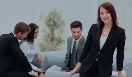 Young business woman standing with her collegues in background a. Successful business women standing with her staff in background at office Stock Photos