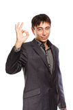 Successful business. Young businessman in dark grey coat and steel-blue shirt standing isolated on white background with okay gesture Royalty Free Stock Image
