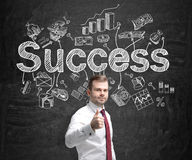 Successful business. A young man holding a thumb up and standing in front of a blackboard with many different business icons and the word 'success' drawn on it Royalty Free Stock Photography