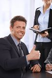Successful businessman. Giving the thumb up, smiling at meeting happily Royalty Free Stock Images