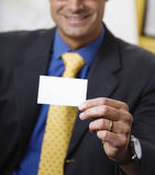 Successful businessman. Work place: successful businessman smiling and holding a white card Royalty Free Stock Images