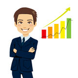 Successful Businessman. Standing with arms folded next to bar chart stats showing business growth trend Royalty Free Stock Photography