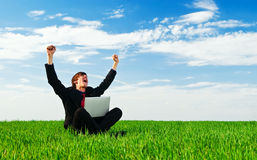 Successful businessman. With laptop sitting at the green grass stock photo