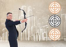 Successful businessman aiming target with bow and arrow. Against digitally generated background Stock Photo