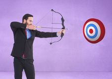 Successful businessman aiming target with bow and arrow against purple background Royalty Free Stock Image