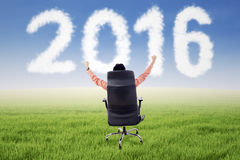 Successful businessman on armchair with numbers 2016 Stock Photo