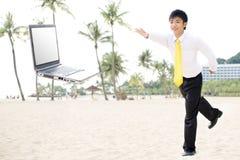 Successful businessman at beach with laptop Stock Photos