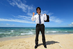 Successful businessman on the beach Stock Images